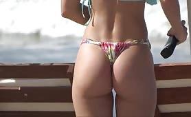 Oiling her ravishing butt in bikini