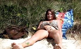 Horny beach babe masturbates her hairy cunt