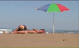 wife gives a handjob to hubby on the beach