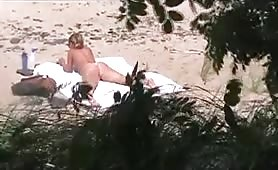 Horny cougar caught masturbating on the beach